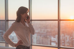Jovem mulher que fala usando o telefone celular no escritório na noite Mulher de negócios fêmea concentrada, olhando para a frent imagem de stock