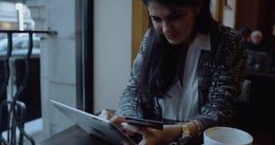 Jovem mulher que faz a compra em linha no tablet pc no café Menina feliz video estoque
