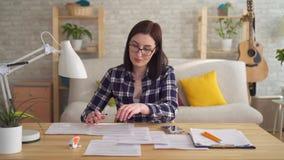 Jovem mulher que faz a contabilidade e o cálculo com a calculadora no desktop filme