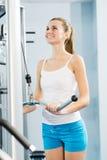 Jovem mulher que faz a corpo-construção no Gym Fotos de Stock Royalty Free