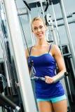 Jovem mulher que faz a corpo-construção no Gym Fotografia de Stock Royalty Free