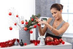 Jovem mulher que faz a decoração do Natal Fotografia de Stock Royalty Free