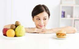 Jovem mulher que faz a escolha entre o alimento saudável e prejudicial Imagens de Stock Royalty Free