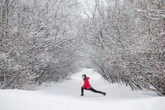 Jovem mulher que faz esticando exercícios durante o inverno imagem de stock royalty free