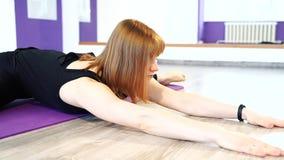 Jovem mulher que faz esticando o exercício em uma esteira em um estúdio da aptidão video estoque