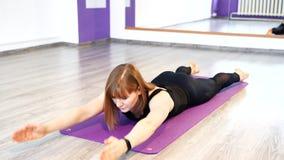 Jovem mulher que faz esticando o exercício em uma esteira em um estúdio da aptidão vídeos de arquivo