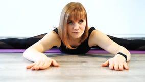 Jovem mulher que faz esticando o exercício em uma esteira em um estúdio da aptidão filme