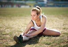 Jovem mulher que faz esticando o exercício, exercício na grama Imagens de Stock Royalty Free