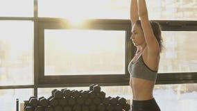 Jovem mulher que faz exercícios com o peso pesado no gym filme