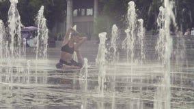 Jovem mulher que faz exercícios da ioga dentro da fonte vídeos de arquivo