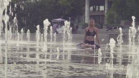 Jovem mulher que faz exercícios da ioga dentro da fonte video estoque