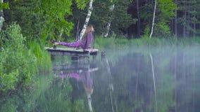 Jovem mulher que faz exercícios da ioga na costa do lago filme