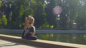 Jovem mulher que faz exercícios da ioga no parque filme