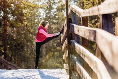 Jovem mulher que faz exercícios durante o treinamento do inverno fora no tempo frio da neve Fotografia de Stock