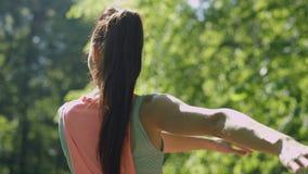 Jovem mulher que faz exercícios e que estica no parque ensolarado
