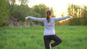Jovem mulher que faz exercícios no campo no nascer do sol video estoque