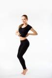 Jovem mulher que faz a ginástica aeróbica e o esticão, isolados no CCB branco Foto de Stock