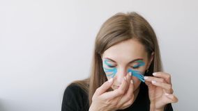 Jovem mulher que faz a gravação em torno dos olhos para rejuvenescer vídeos de arquivo
