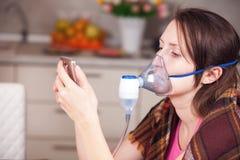 Jovem mulher que faz a inala??o com um nebulizer em casa fotos de stock