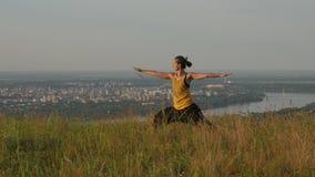 Jovem mulher que faz a ioga do verão em um monte acima da cidade de Novi Sad, gora de Fruska, Sérvia video estoque
