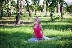 Jovem mulher que faz a ioga e a ginástica no parque Fotos de Stock Royalty Free