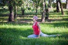 Jovem mulher que faz a ioga e a ginástica no parque Fotografia de Stock