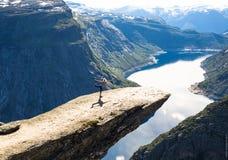 Jovem mulher que faz a ioga em Trolltunga A menina feliz aprecia o lago bonito e o bom tempo em Noruega Imagens de Stock