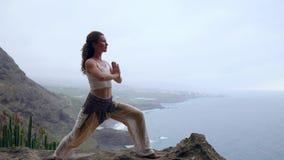 Jovem mulher que faz a ioga em um litoral rochoso no por do sol O conceito de um estilo de vida saudável harmonia Ser humano e na video estoque