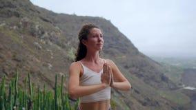 Jovem mulher que faz a ioga em um litoral rochoso no por do sol O conceito de um estilo de vida saudável harmonia Ser humano e na filme