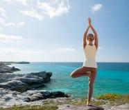 A jovem mulher que faz a ioga exercita fora imagem de stock