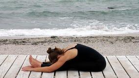Jovem mulher que faz a ioga no beira-mar filme