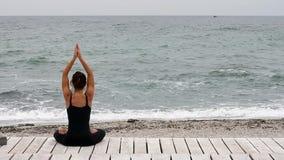 Jovem mulher que faz a ioga no beira-mar video estoque