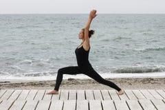 Jovem mulher que faz a ioga no beira-mar na manhã no dia de verão imagens de stock