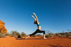 Jovem mulher que faz a ioga no deserto Fotografia de Stock