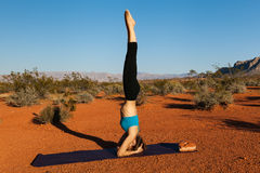 Jovem mulher que faz a ioga no deserto no tempo do por do sol Imagens de Stock Royalty Free