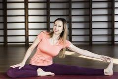 Jovem mulher que faz a ioga no tapete no sal?o imagem de stock