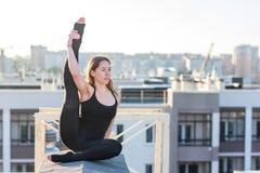Jovem mulher que faz a ioga no telhado fotos de stock