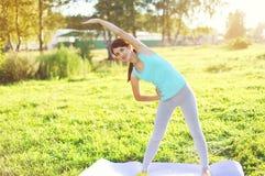 Jovem mulher que faz a ioga que estica exercícios na grama Fotografia de Stock