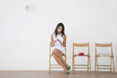 Jovem mulher que faz malha na sala de espera Imagens de Stock Royalty Free