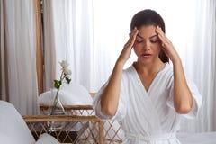 Jovem mulher que faz massagens sua cara fotografia de stock royalty free