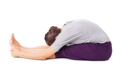 A jovem mulher que faz o asana da ioga assentou a curvatura dianteira Paschimottanasa Foto de Stock
