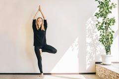 Jovem mulher que faz o asana no estúdio da ioga Imagens de Stock Royalty Free