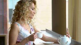 Jovem mulher que faz o autorretrato em sua câmara digital esperta do telefone ao sentar-se no café durante a pausa para o almoço vídeos de arquivo