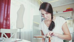 Jovem mulher que faz o bordado decorativo na aro filme
