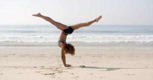 Jovem mulher que faz o Cartwheel na praia imagens de stock royalty free