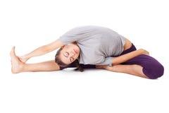 Jovem mulher que faz o exercício da ioga isolado no branco Foto de Stock