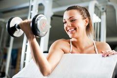 Jovem mulher que faz o exercício do bíceps fotografia de stock royalty free