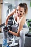 Jovem mulher que faz o exercício do bíceps imagem de stock