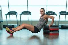 Jovem mulher que faz o exercício do tríceps em deslizante Fotografia de Stock