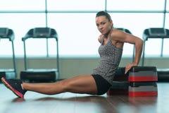 Jovem mulher que faz o exercício do tríceps em deslizante Foto de Stock Royalty Free